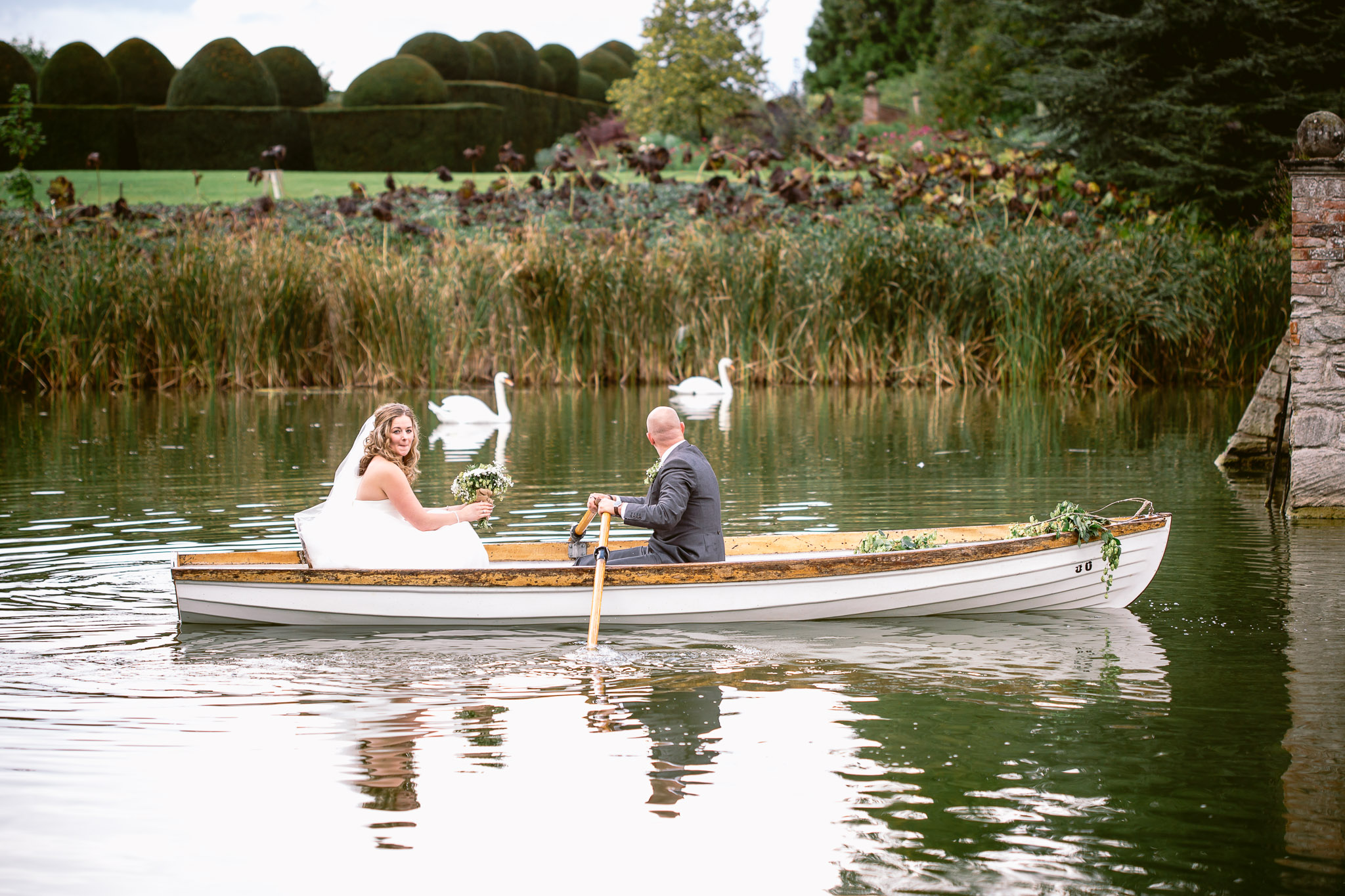 bride and groom on the boat in birtsmorton court with swans in the background