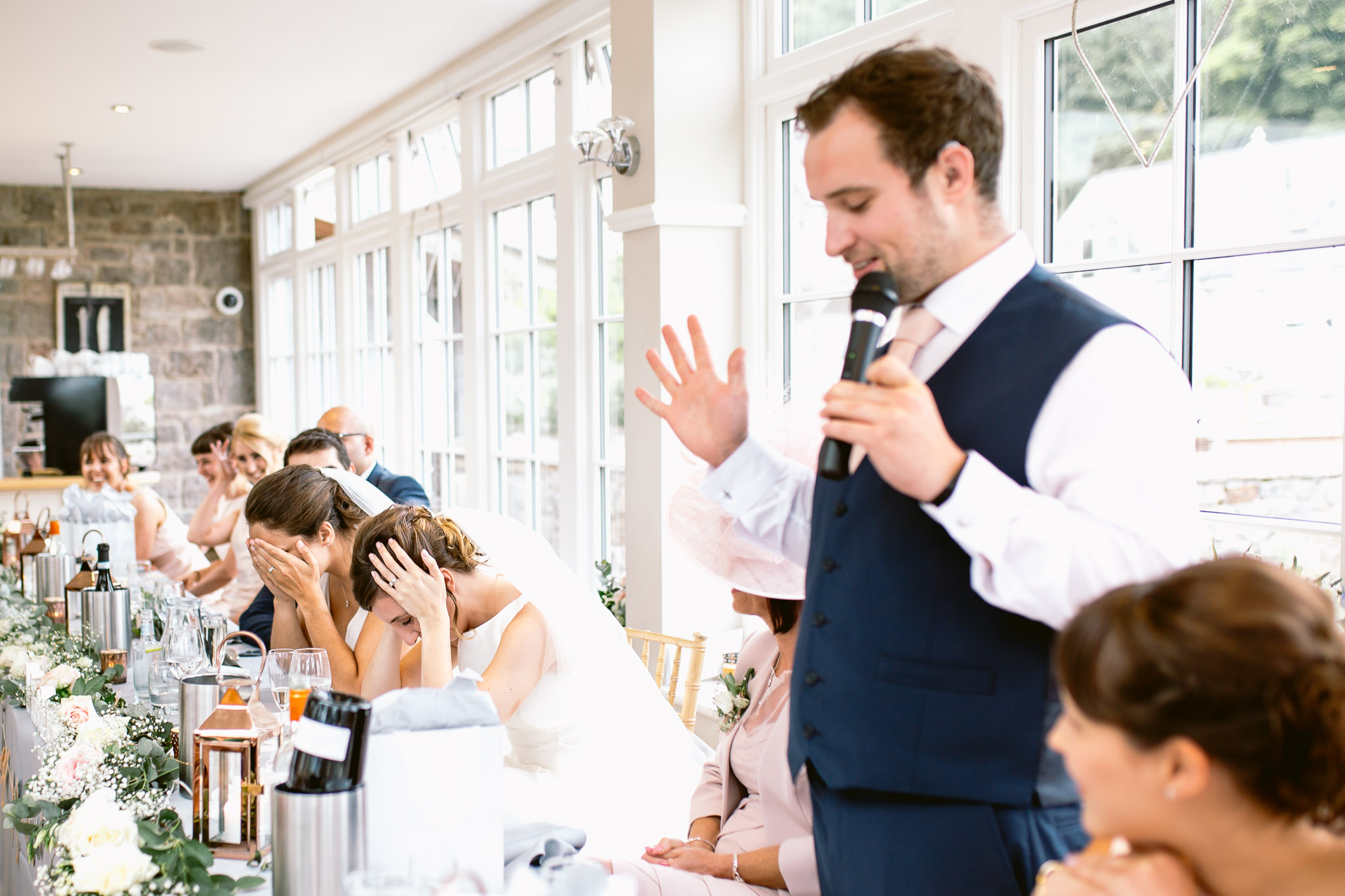two brides covering their ears during the best man speeches