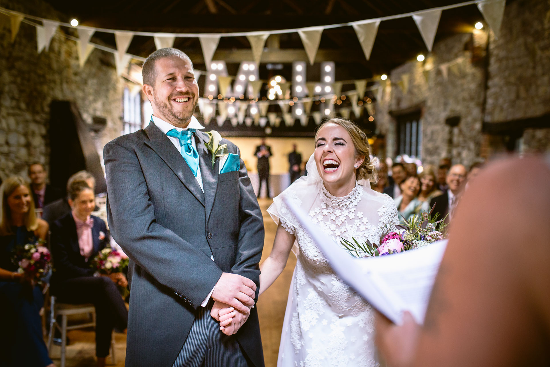 bride and groom bursting with laughter at the wedding ceremony in Pencoed House