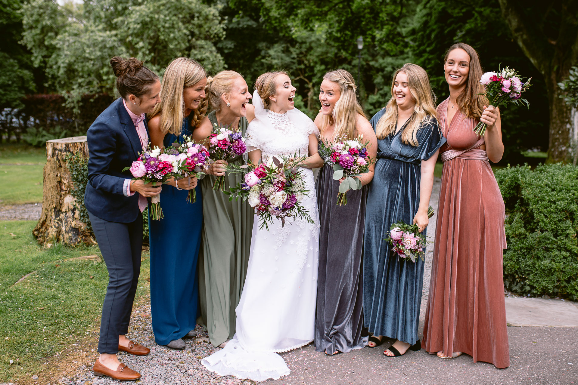 bride and her bridesmaids standing with flowers and laughing in front of Pencoed House wedding