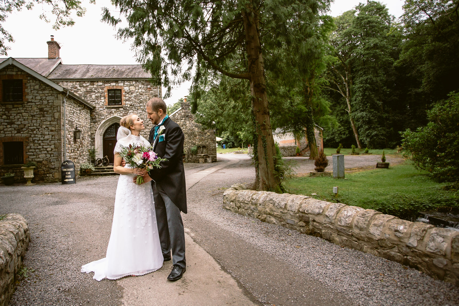 bride and groom standing and hugging in front of Pencoed House wedding venue