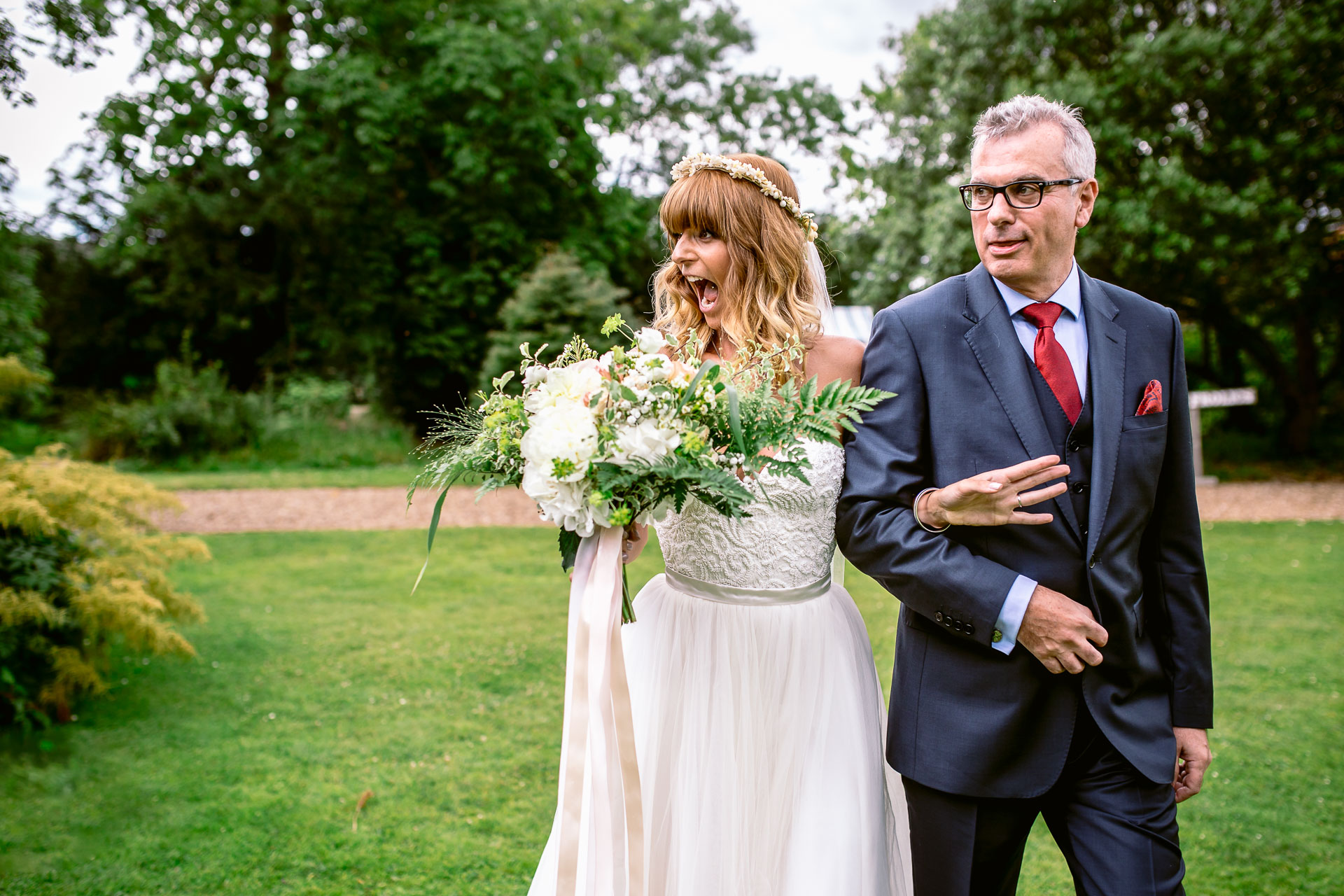 preston court boho wedding alexia and dan bride is walking down the aisle and laughing