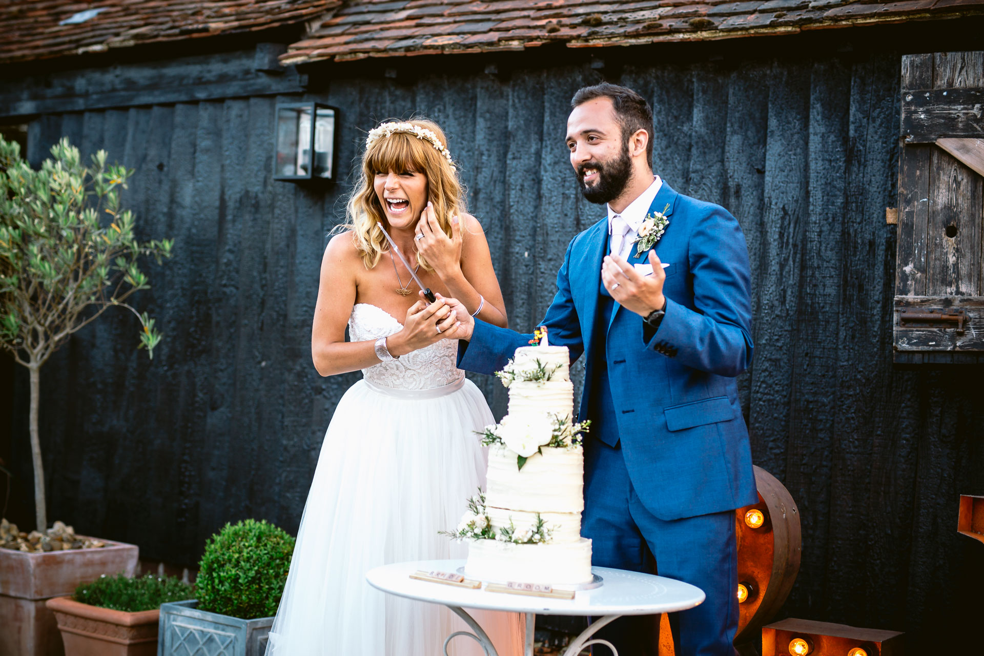 preston court boho wedding alexia and dan bride and groom cutting a wedding cake and laughing