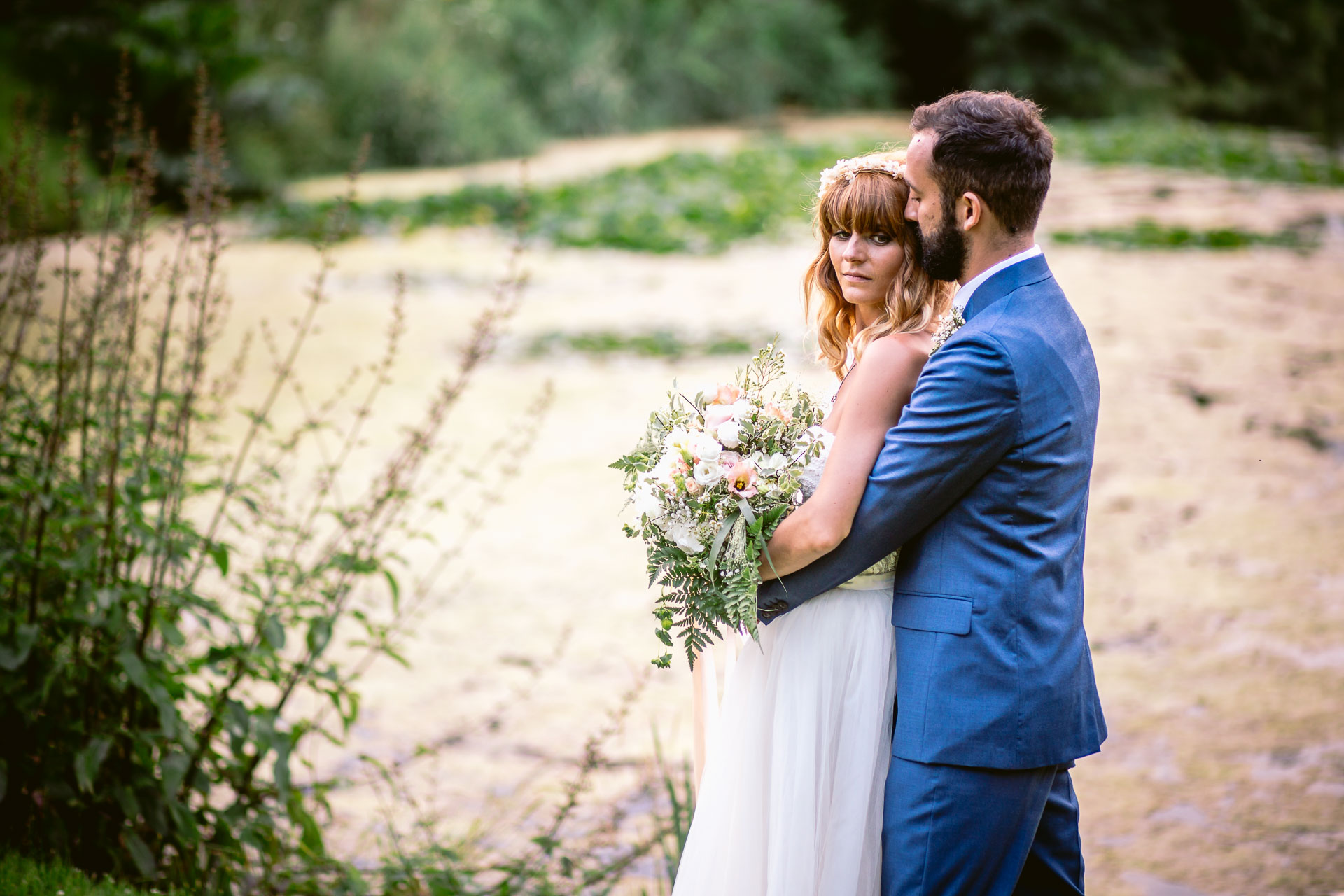 preston court boho wedding alexia and dan bride and groom standing by the lake and hugging each other