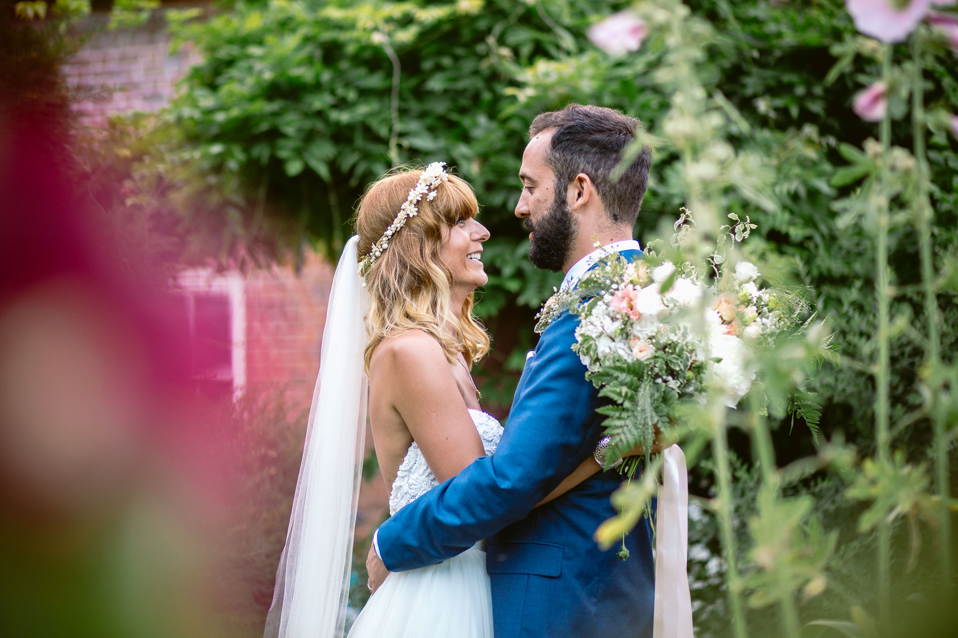 preston court boho wedding alexia and dan bride and groom standing in the flower field and looking at each other