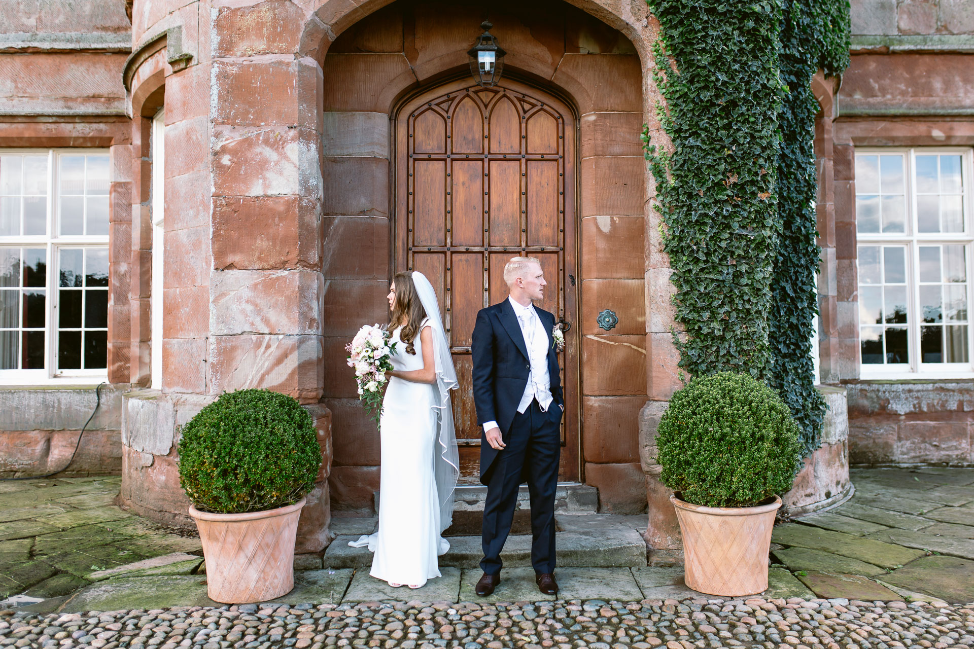 The Citadel wedding Shropshire Sarah-Jane and Steve bride and groom standing at the venue door and looking opposite directions