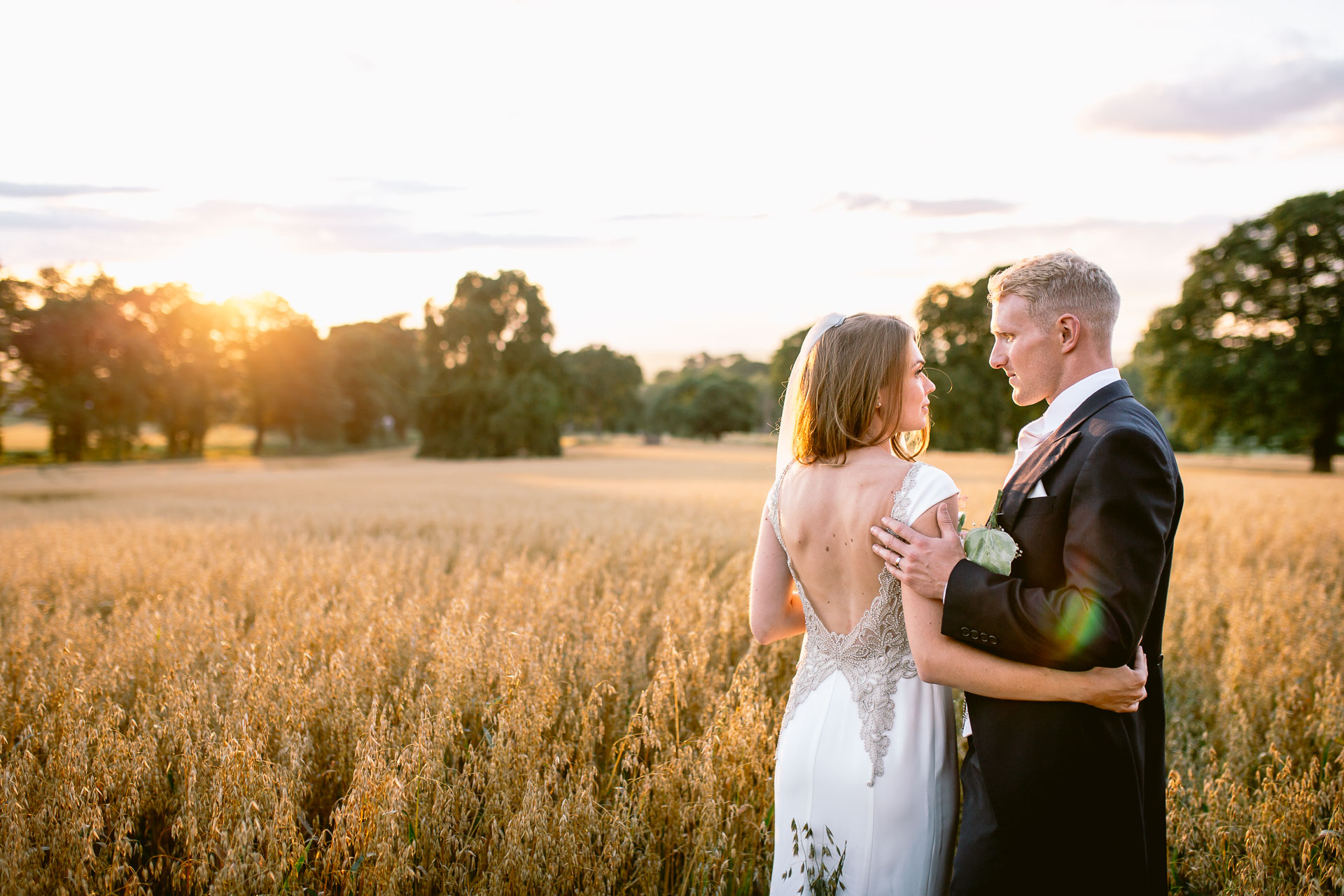 The Citadel wedding Shropshire Sarah-Jane and Steve bride and groom standing in the fields go gold in the sunset looking at each other