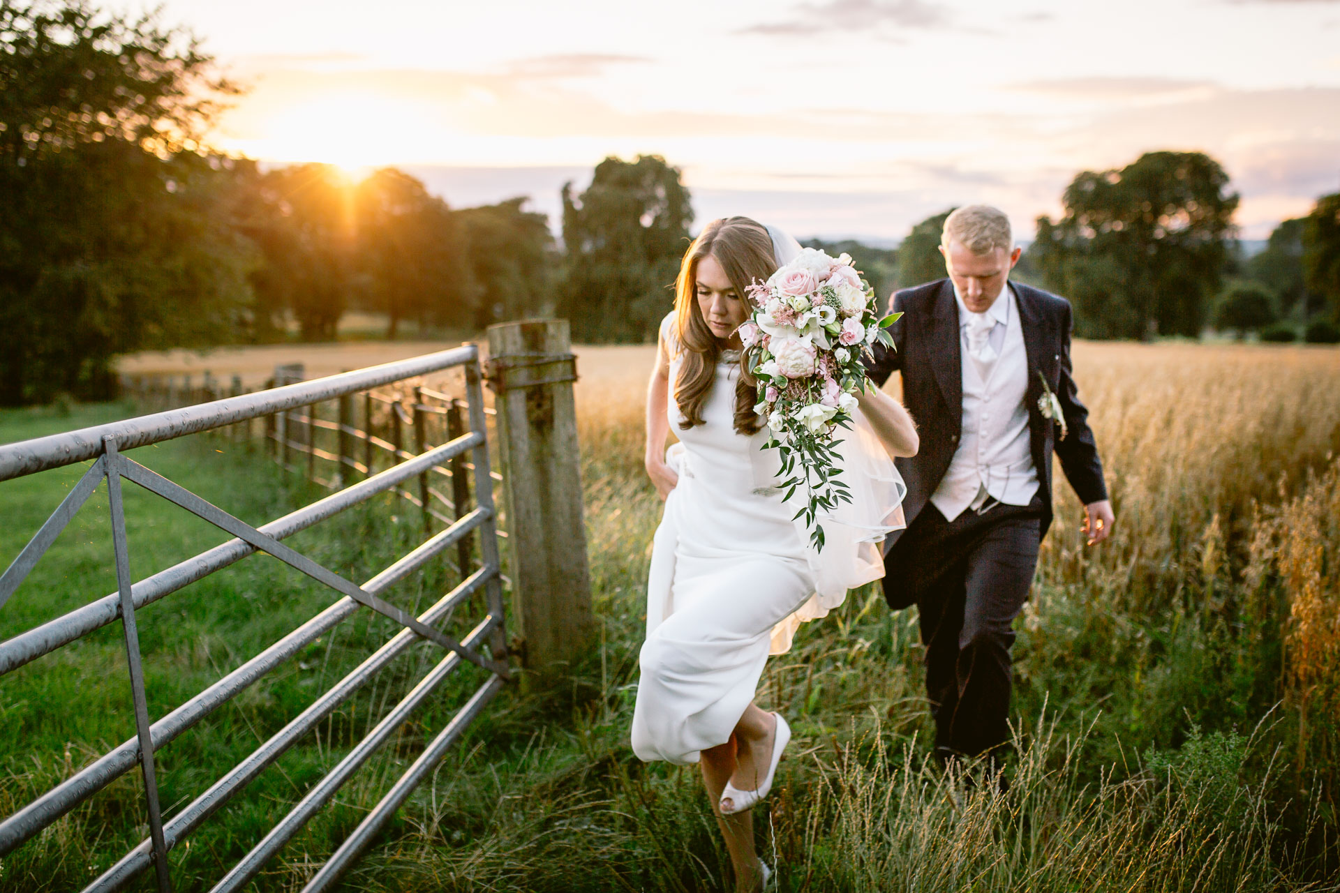 The Citadel wedding Shropshire Sarah-Jane and Steve bride and groom walking through the gate in the sunset